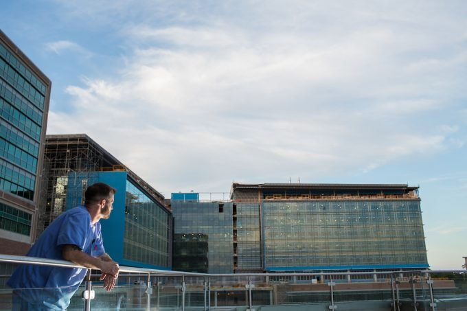Michael Gross, R.N., a UF Health Shands Hospital Neuro ICU Unit 82 nurse, looks out at the construction site of the heart and neuro hospitals. He is one of hundreds of staff members who will transition to the new space in late 2017. Photo by Mindy Miller.